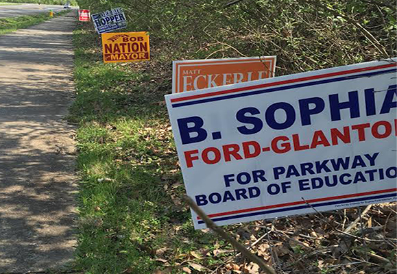 Campaign signs for the upcoming Parkway school board election pile up along the side of Baxter road.