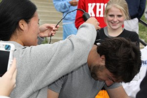 Senior Kyoung Lee shaves Coach Charlie Cutelli's head over the trash can while junior Yvonne Krumrey looks on.