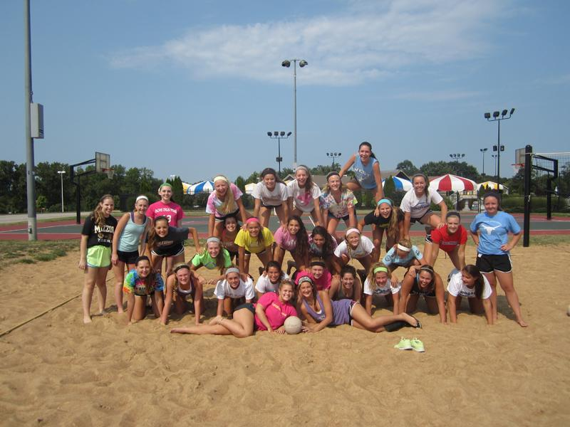 The volleyball team makes a pyramid after playing sand volleyball at Manchester Park, Saturday, August 17.  The program met at 9 a.m., ate a bagel breakfast and tie dyed team t-shirts.