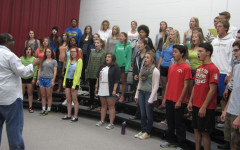 """Eric Anthony conducts choir. """"Choir is full of so many great things. It is a comfortable place for kids to express themselves and practice their leadership. Along with that, it helps boost self confidence when preforming in front of a crowd. We explore poetry, literature, history and different cultures,"""" Anthony said."""