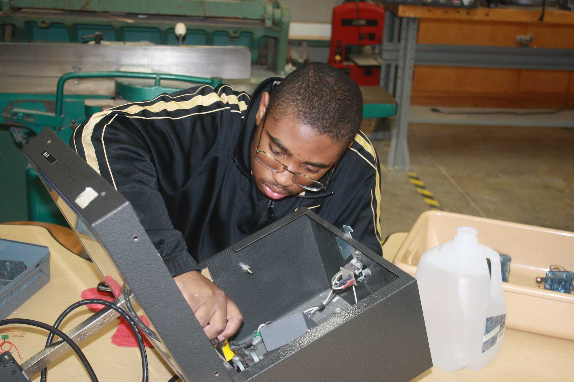 Junior Darrion Ward works on fixing an old projector to use the spare parts in the robotics class