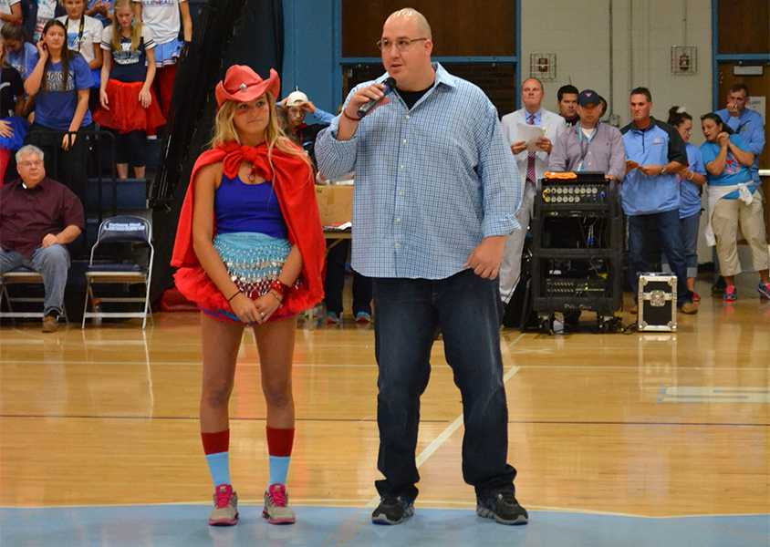 Junior Mary Galkowski and Sergeant Joshua Eckhoff  walk into the middle of the gym during the fall pep rally.