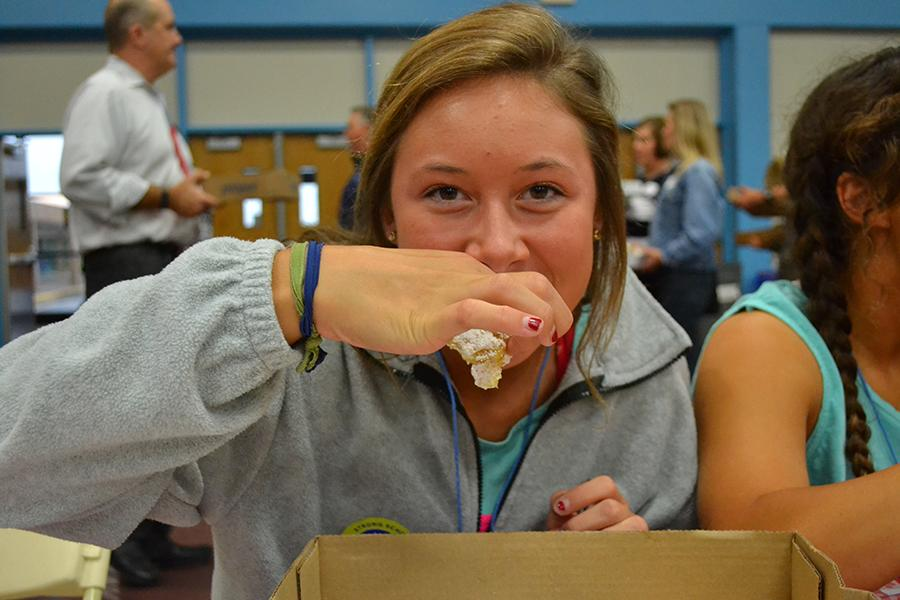 Biting into a lemon bar, Junior Julia Patterson enjoys the food and her friends at  Taste of West.