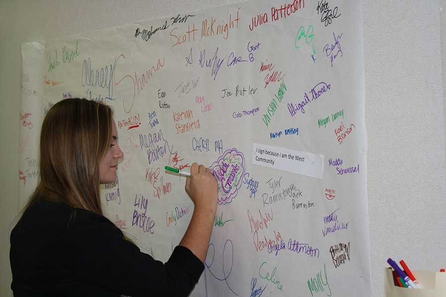 Freshman Katie English signs a poster in front of Mrs. Kerpash's room pledging to be
