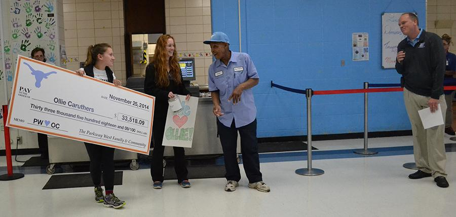 During first lunch, juniors Emily Wind and Shannon Anderson give Custodian Ollie Caruthers a check for 33K.