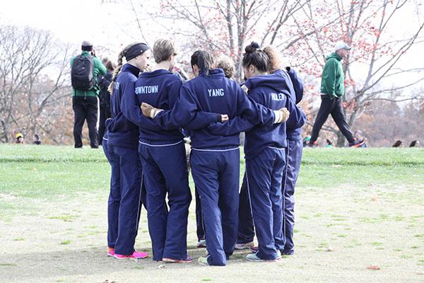 Huddling before the race, the girls cross country team chants
