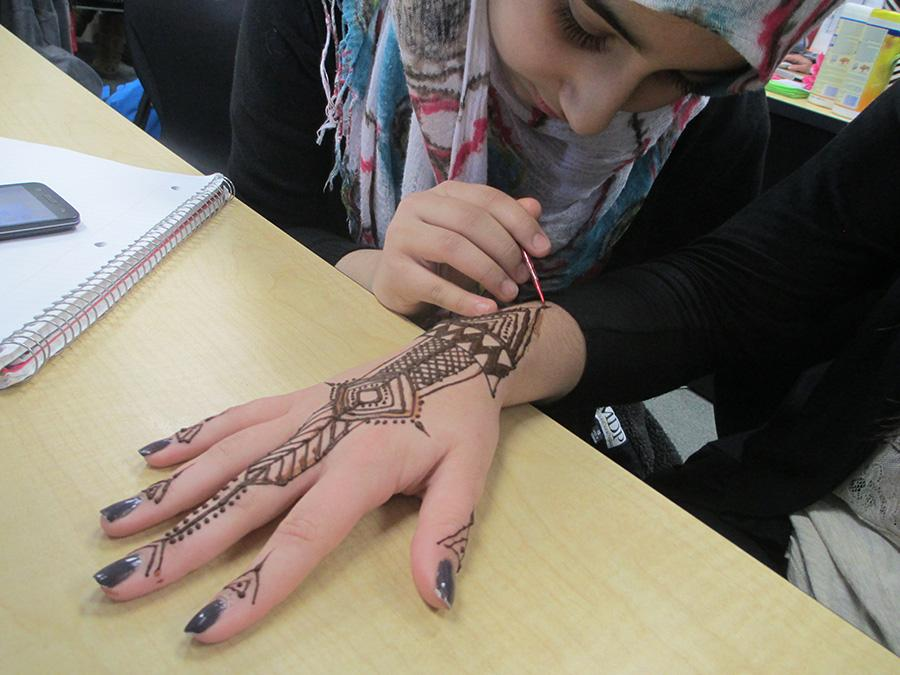 Sophomore Meamuna Paracha designs a henna tattoo.