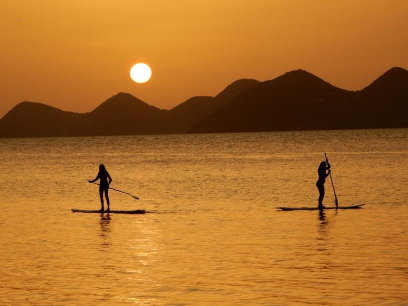 On the British Virgin Islands, junior Megan Barton and Corinne Schillizzi paddle board.