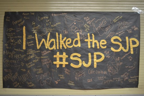 Students signed a poster after a silent protest to show their support for social justice.