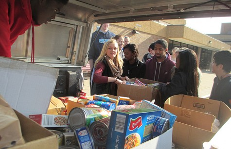 Students aid Mrs. Annie Wayland as they put boxes of donations from the canned food drive in the back of a truck to be taken to Circle of Concern.