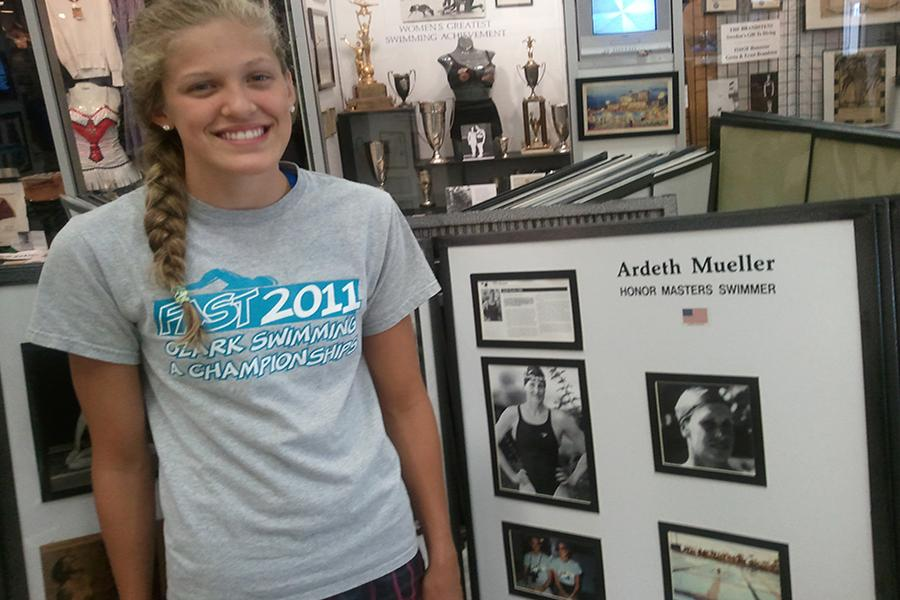 Sophomore Evie Pfeiffer stands by her grandmother, Ardeth Mueller's, exhibit at the International Swimming Hall of Fame in Fort Lauderdale, Fl.  Pfeiffer's grandmother went to the 1956 Olympic Trials in Detroit for the 100m fly, placing eighth in the nation.