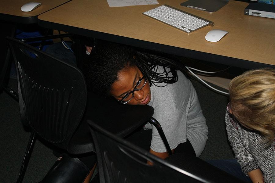 Following the Intruder Drill procedure, junior Vericia Pearson hides underneath the desk.