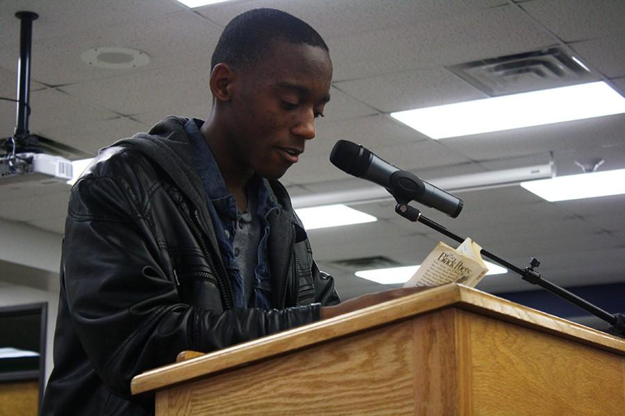 "During the 13th annual African American Read-In in the West High library, junior Donte Hopkins reads ""Love Your Enemy"" by Yusef Iman.  Pizza and dessert was served to all student present. ""We all have to live together.  In the past there was so much hatred.  The poem is telling everyone not to forgive them for everything they have done, but instead love them.  It represented how we have to keep moving forward and love each other no matter what happens,"" Hopkins said."