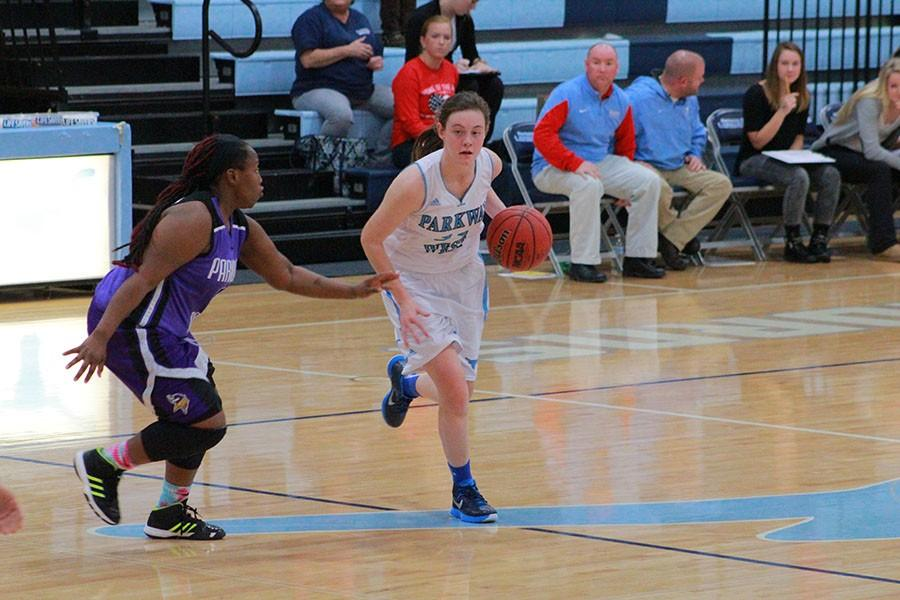 Dribbling the ball down the court, senior Lee McMullin defends the ball from Parkway North.