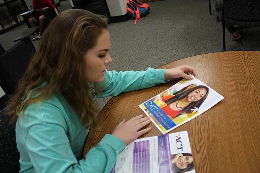 Junior Sarah Burnham looks over ACT and SAT information in the College and Career Center.