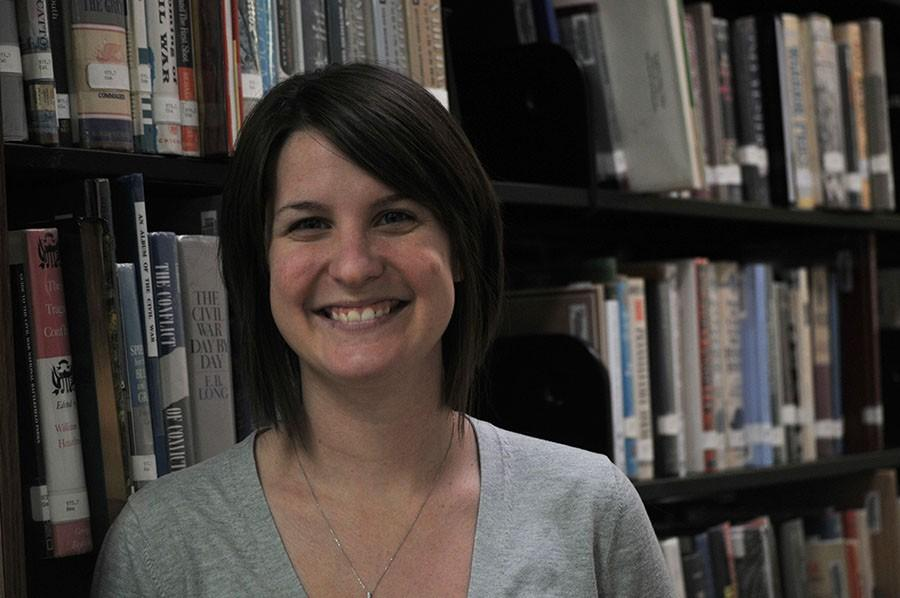 Librarian+Lauren+Reusch+poses+in+the+library.+