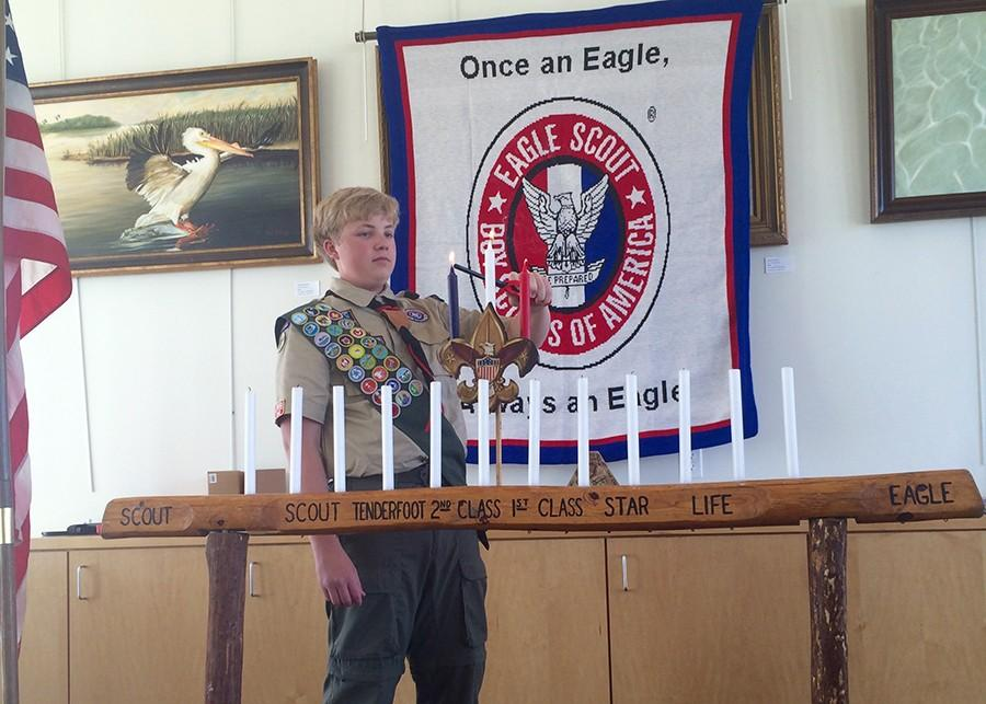 Christopher Narishkin lights the red, white and blue candles to symbolize what he will do to honor his expectations as an Eagle Scout.