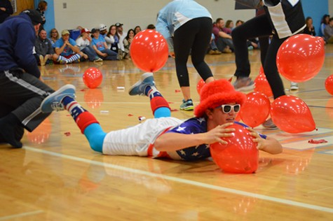 Junior Alex Karrenbrock lays on a balloon to get it to pop in order to win the competition to spell PWEST first.