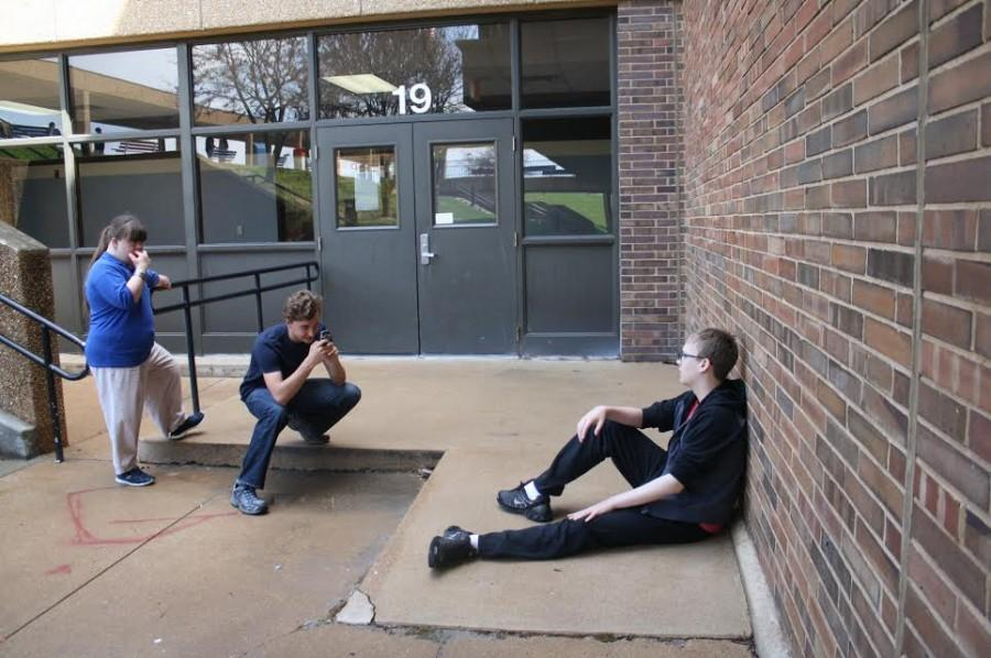 "Senior Lindsey Hacker, freshman Alex Volz and freshman Jack Vaughan shoot two films with different styles in front of the school. The first film featured Vaughan as a crazy man visiting a shrink. ""The second one was a musical about Jack, as the original crazy man, roaming the streets thinking he's completely sane,"" Volz said."