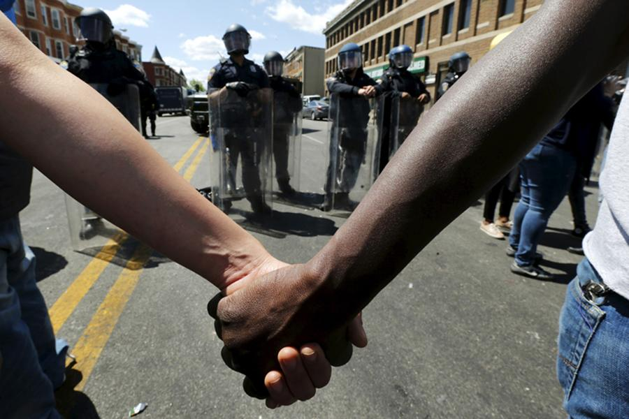 In order to stop the violence in Baltimore, people linked hands, keeping the protestors from the police.