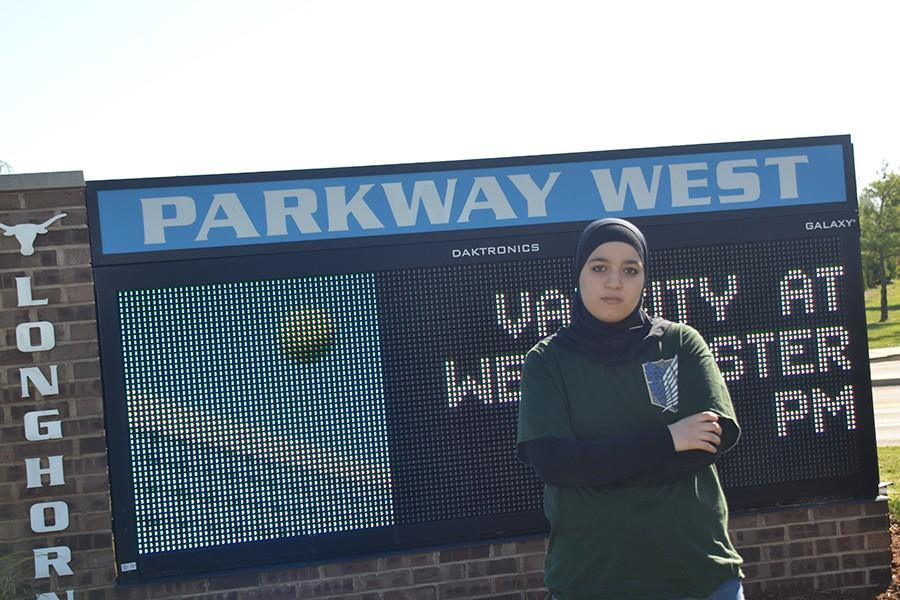 """Junior Sarah Hima stands in front of West's welcome sign. """"I'm not sure why we weren't on the Post-Dispatch list initially,"""" Hima said. """"We're a hardworking school, and I feel like we should have earned a place."""""""