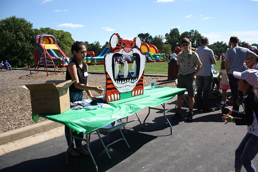 Volunteering at the Green Trails fall carnival, sophomore Sarah Habibollah tosses a bean bag to an elementary student.