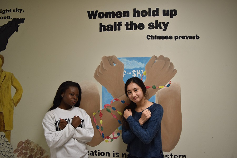 Junior Alyssa Jackson, a Women of West Executive Board member, and freshman Maddie Cooke, a Feminist Club member, pose in the history hallway.