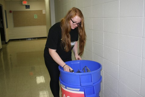 Sorting through the can food drive bin, junior Mallory Garrett removes cans from bags.