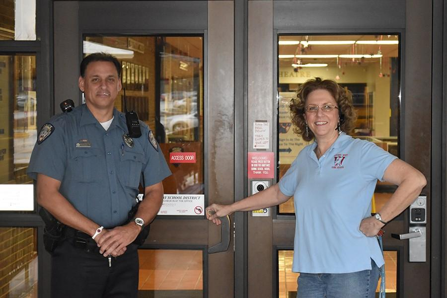 School Resource Officer Scott Scoggins and Front Office Receptionist Vickie Hankammer stand outside the access door.