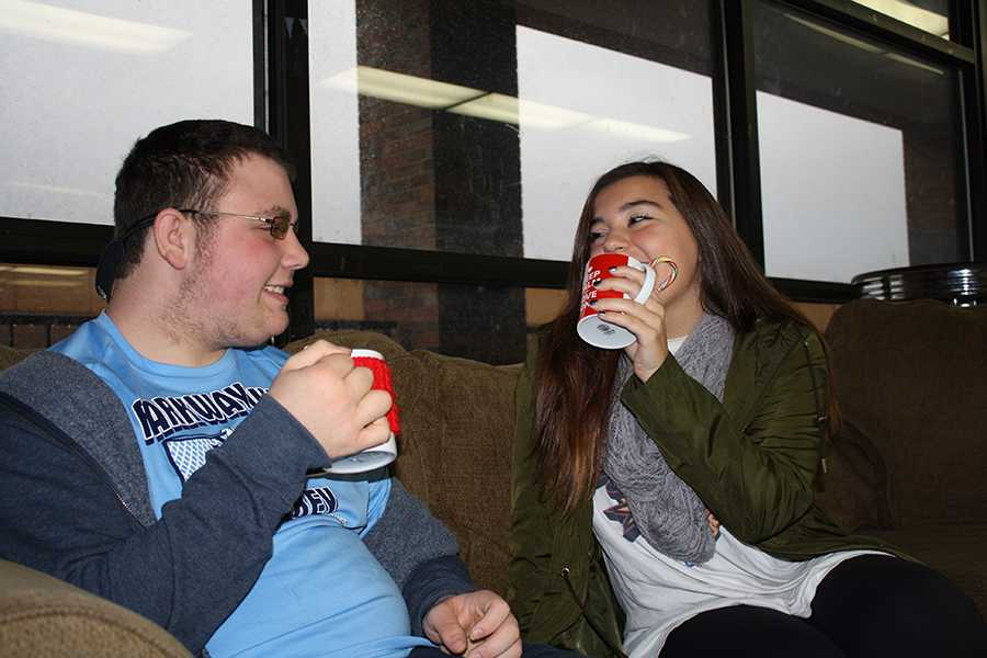 Junior Tyler Hannegan and Senior Ally Guccione sit on a couch and enjoy the popular holiday drink, peppermint hot chocolate.