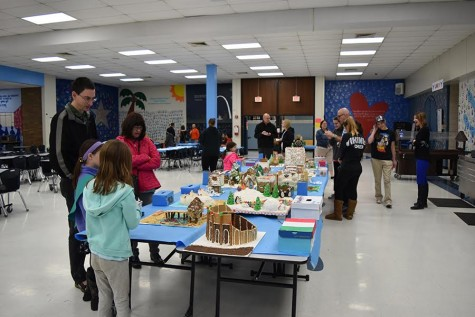 Parents and children admire the different houses from different schools.