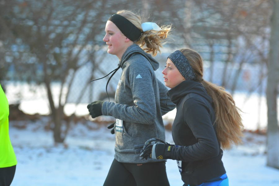 Butler and Osborne run together before the eighth mile-marker, Osborne sporting West's blue cross country bow. With temperatures skimming 32 degrees, both runners wore headbands to guard their ears from the wind.