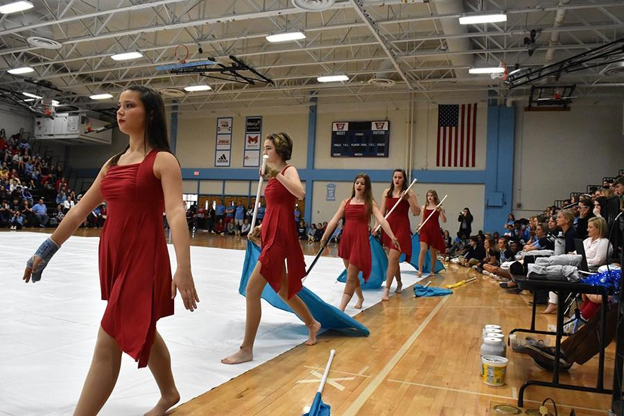 """Dressed in red, Winter Guard parades across the gym with their flags in hand. The winter guard performed their dance to the song """"Boom Clap"""". """"My favorite dance move is the pop toss which is when we all throw our flags up at the same time. It was one of the big ensemble moments of the performance,"""" freshman Deirdre Jost said. Winter Guard has competed in four competitions so far."""