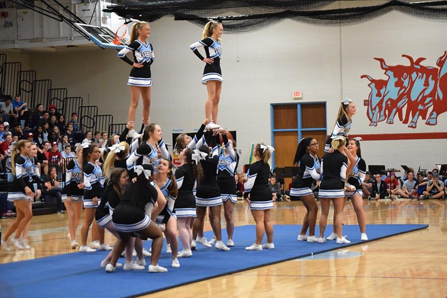 """West's Cheerleading squad performs a pyramid for the student body. The cheerleaders spent several late nights perfecting the performance. """"It was a little nerve-racking being at the top since I didn't want to mess it up in front of the whole school or ruin it for the team,"""" freshman and flyer Sophie Pellegrino said. The cheerleading squad also performed in the fall pep rally."""