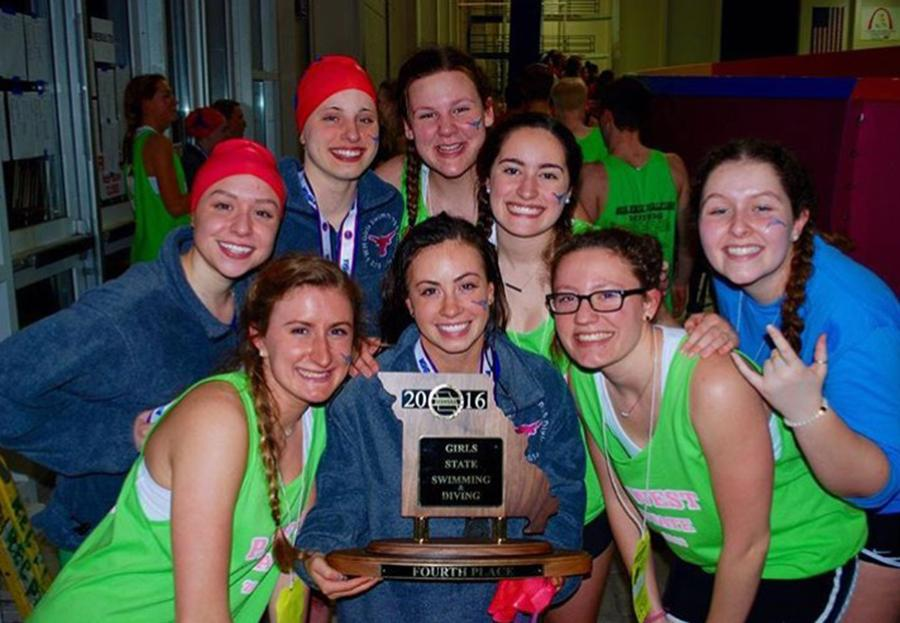 Swimmers pose with fourth place trophy.