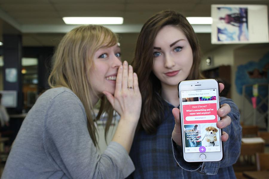 "Senior Abby Larsen and sophomore Kennedy Brown pose in the library with the app, Whisper. The app has over 87 users from West so far.  ""I think most of the time when people first hear about it they think it's mostly for negative things because that's how most anonymous apps work. But on Whisper, there is a place for just our school. That's where I am most of the time. Everywhere else, there are mean comments, but mostly at our school it's just positive things,"" Brown said."