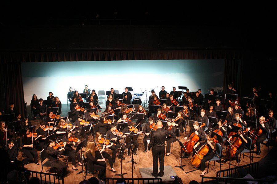 Directing the orchestra at in the theater, Mr. Sandheinrich waves his arms to conduct his students.