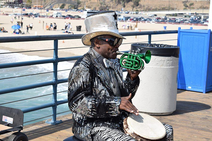 Lenny+Hoops%2C+circus+performer%2C+shares+his+life+story+on+the+Santa+Monica+Pier+to+a+group+of+high+school+students+on+April+13.+Hoops+stopped+playing+music+for+the+crowd+and+emphasized+the+importance+of+finding+yourself+through+adventure+and+opportunities+outside+of+one%27s+hometown.+%E2%80%9CWhen+you+graduate+high+school+that+is+your+only+opportunity+to+see+the+world.+You+can+always+come+back+home%2C+but+you+must+get+out%2C%E2%80%9D+Hoops+said.