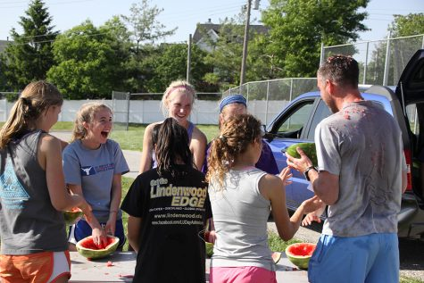 """Cleaning out their watermelon helmets,  freshman Claire Smout, sophomore Betsy Wait, juniors Maggie Hulen and Maggie Morse, seniors Rachel Osborne, and Abby Allgeyer, and Coach Kevin John, prepare to put the melon shells on their heads. """"I was one of the first people to transform their watermelon into a watermelon hat,"""" Osborne said. Osborne drove home wearing the watermelon hat that evening."""