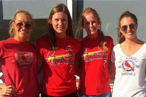 Seniors Maddie Kaempfe, Maggie Walkoff, Jamie Gardner and Lauren Sanford pose for a picture in their Cardinals gear at the Royals game.