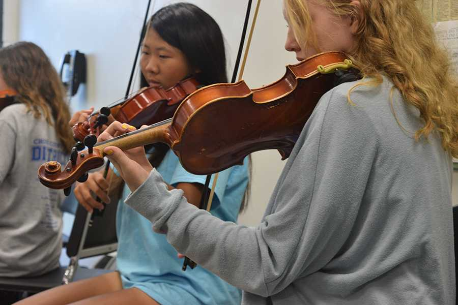 Juniors Sydnee Yap and Emma Richards rehearse in the first violin section of the Symphonic Orchestra.