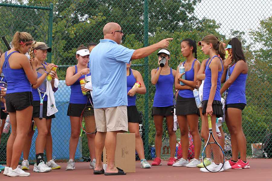 Coach Jason Townsend talks to the girls varsity team before a round of matches.