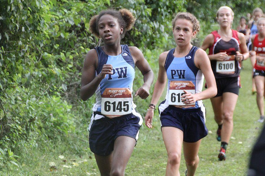 Racing ahead, varsity runners and seniors Rikita Saunders and Maggie Morse compete at the Stan Nelson Invitational.