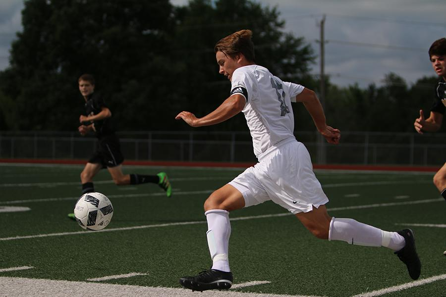 Making his way down the field, junior Jack Galkowski prepares to shoot the ball into the goal. The boys played in the Northwest tournament against Oakville on Aug. 20 with an ending score of 0-3.