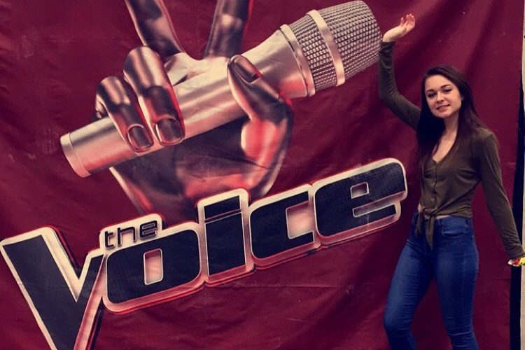 Sophomore Alyssa Dohm poses next to the banner after her audition for The Voice on Feb. 16