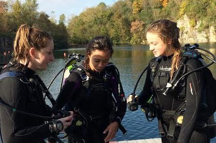 Senior Anna Mae Atkins, junior Emily Dickson, and sophomore Hayden Sampson check their gear after the last dive at Mermet Springs.