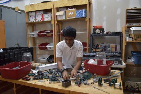 Reaching for a gear, freshman Bhargav Addagarla builds a robot.