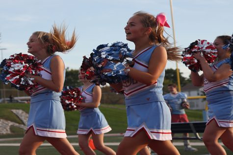 Rallying the crowd, competition cheerleaders freshmen Kelsey Long, Lauren Adam and Sophie Gulino support the football team with the JV team.