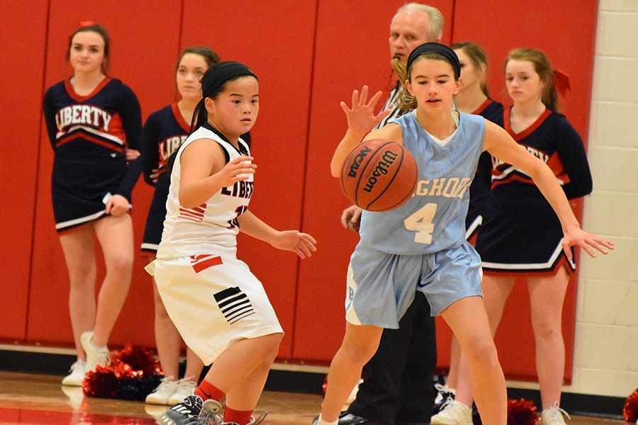 Freshmen Emily Lofgren runs to maintain possession of the basketball against Wentzville Liberty High School on Dec. 15.