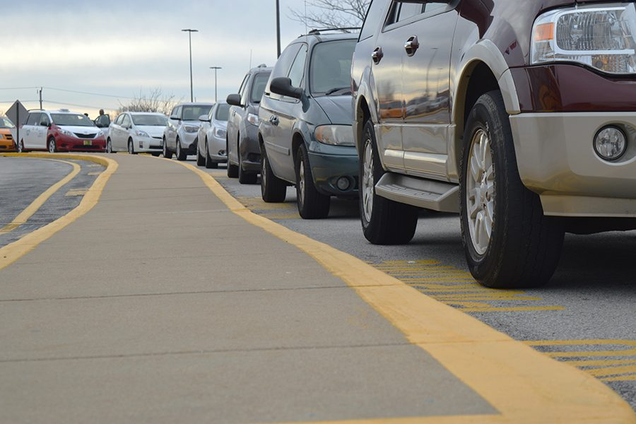 A long line of cars wait in the parking lot to exit the school.